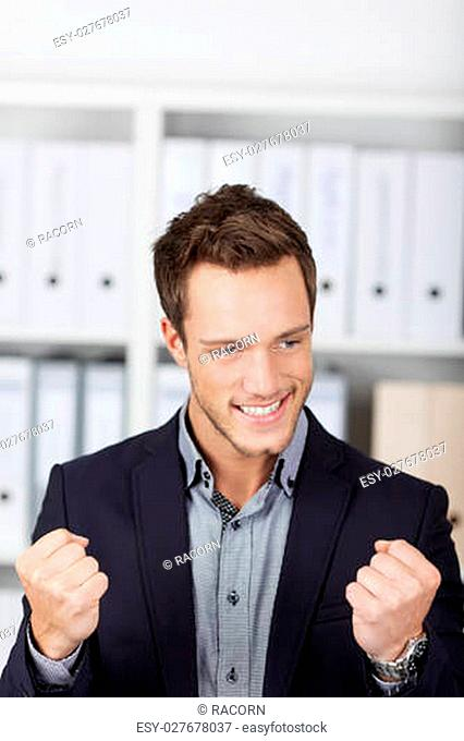 Successful young businessman clenching fists at the office