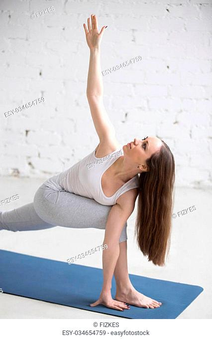 Attractive happy young woman working out indoors. Beautiful model doing exercises on blue mat in room with white walls. Twisting Side Angle Pose