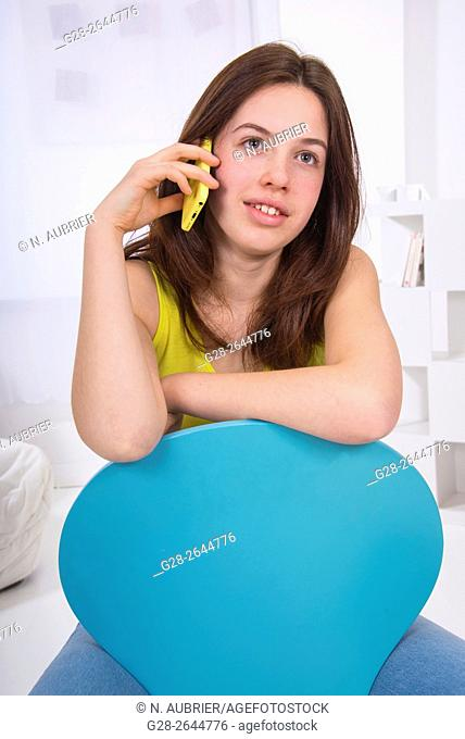 Teenage girl using a cellphone, sitting astride a blue chair