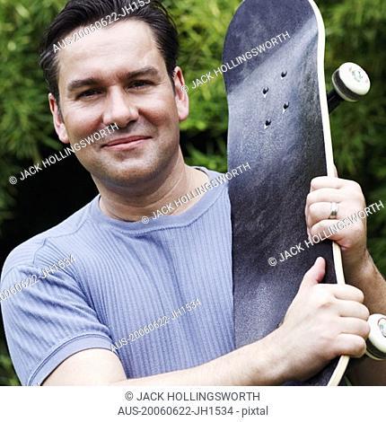 Portrait of a mature man holding a skateboard