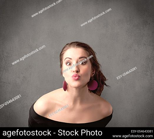 A pretty young teenage girl standing in front of a grey clear empty urban wall background concept while making funny faces