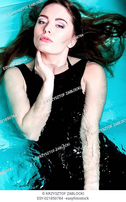 Woman floating on swimming pool in black dress