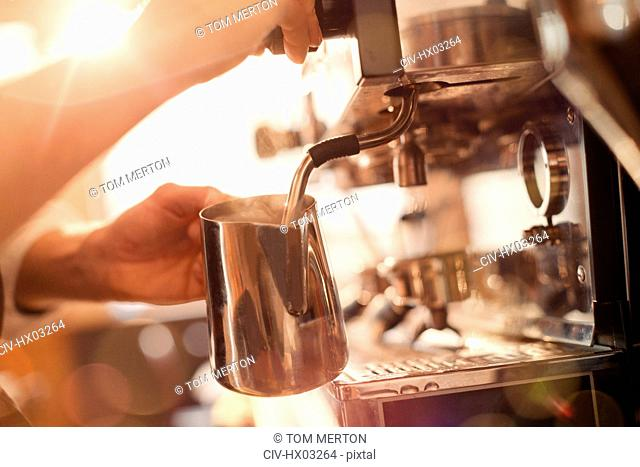 Close up barista using espresso machine milk frother