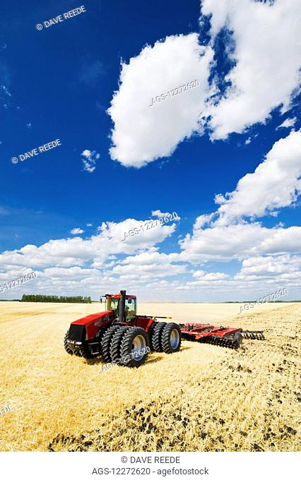 A tractor pulling a disc harrow works soil containing barley stubble, near Lorette; Manitoba, Canada