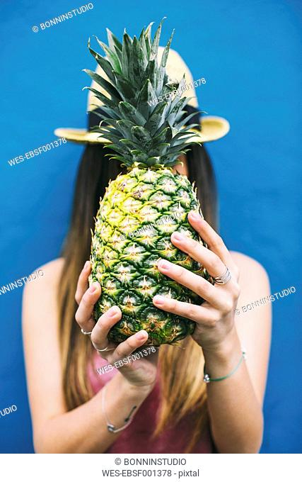 Young woman holding pineapple in front of her face