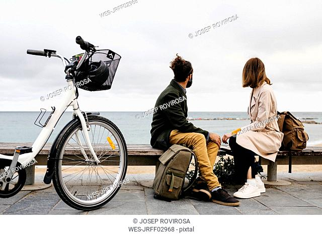 Couple sitting on a bench at beach promenade next to e-bike looking at the sea