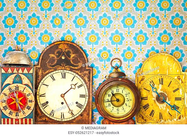 Colorful vintage clocks in front of retro wallpaper with flower print