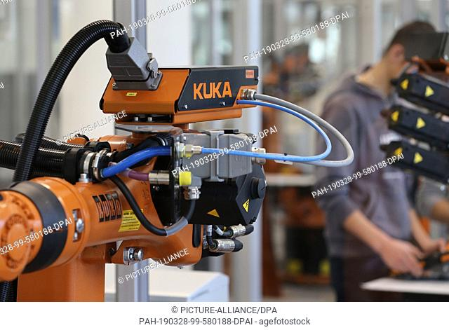 28 March 2019, Bavaria, Augsburg: Customers of the robot manufacturer Kuka are standing at a Kuka robot in the Kuka College