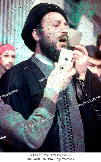 View of a man dressed in traditional clerical robes and black turban, speaking into a microphone at a rally in Iran, March, 1983
