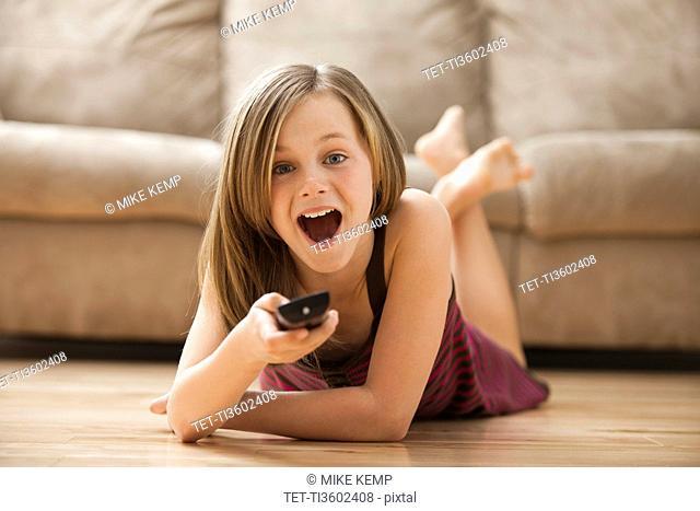 USA, Utah, Lehi, Girl 10-11 lying on floor, watching TV