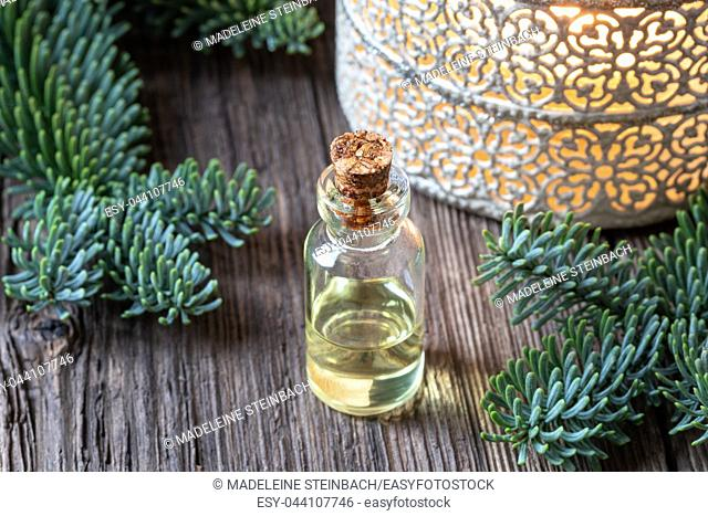 A bottle of essential oil with fresh fir branches