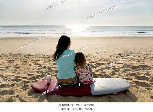 Mother and daughter sitting on surfboard at beach