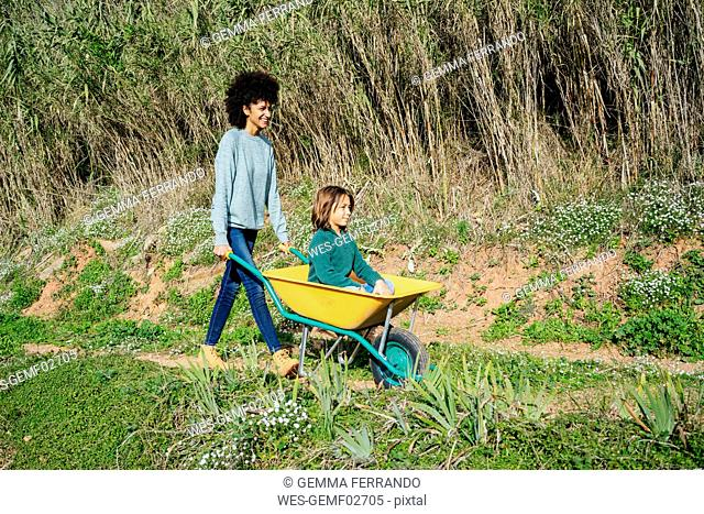 Father walking on a dirt track, pushing wheelbarrow, with his son sitting in it