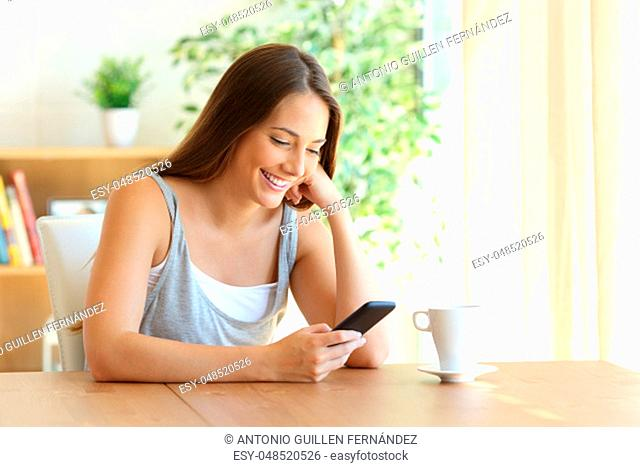 Girl reading sms on line in a smart phone sitting in a table at home with a warm light from a window in the background