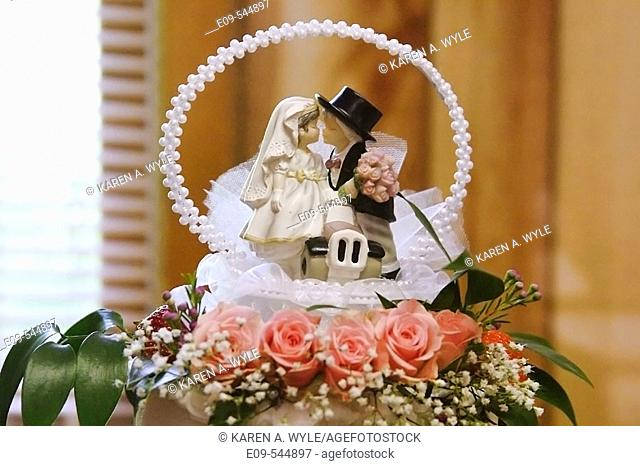 Wedding cake decoration with groom with top hat, arch of pearls, lace and flowers, fruit and leaves; wall and window out of focus in background