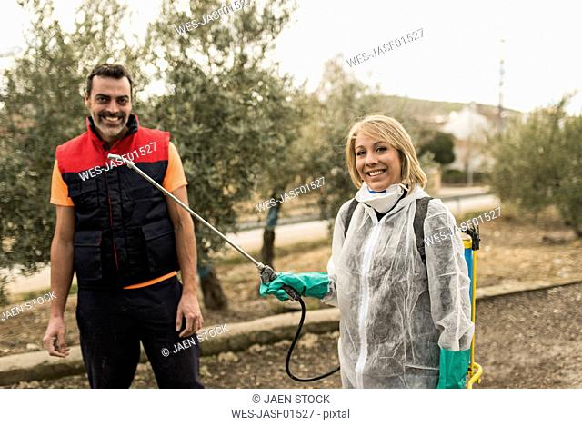 Couple working on farm, woman wearing protective overall to fumigate olive trees