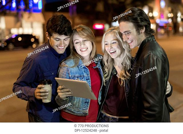 A group of four friends huddle together on a sidewalk looking at a tablet as the glow from the screen lights up their faces; Edmonton, Alberta, Canada