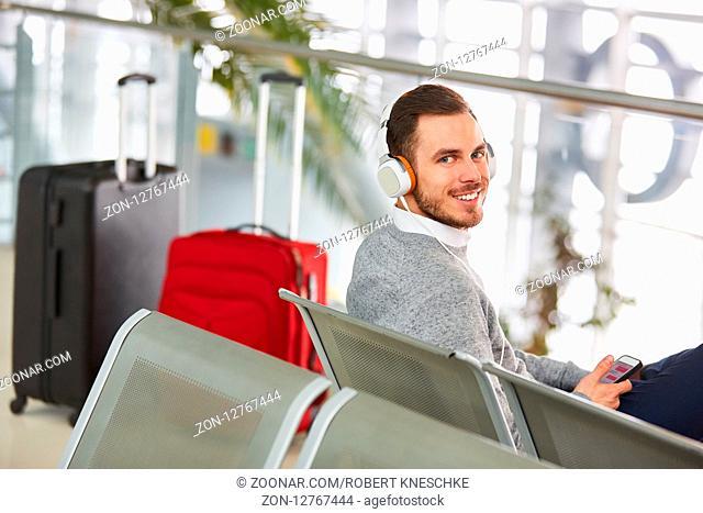 Mann als Passagier im Wartebereich im Flughafen hört Musik über Kopfhörer und Smartphone