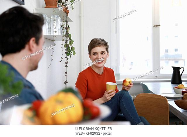 couple sitting in kitchen, talking, woman eating apple