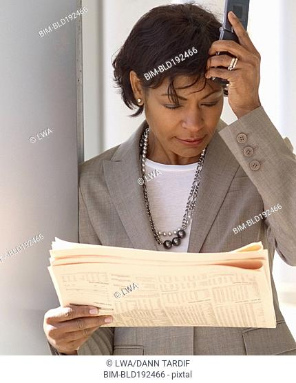 Frustrated African businesswoman reading newspaper