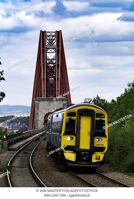 View of Scotrail passenger train approaching Dalmeny Station after crossing Forth Railway Bridge in Lothian , Scotland, United Kingdom