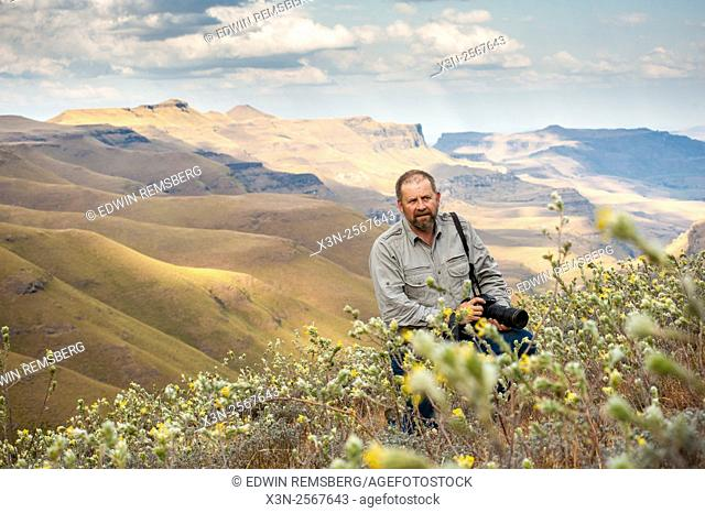 Man with a camera standing amongst the wildflowers with rolling hills in the background in Sani Pass, between South Africa and Lesotho