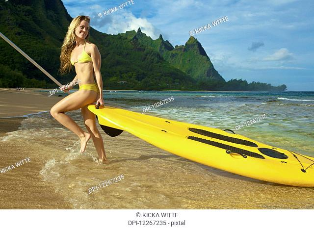 Young woman with stand up paddle board; Kauai, Hawaii, United States of America