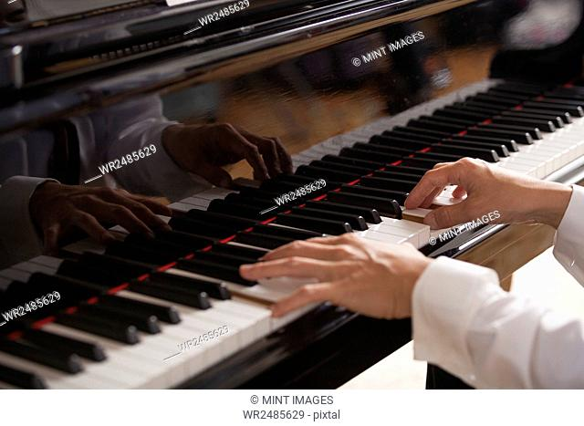 Close up of a pianist's hands, playing on a grand piano