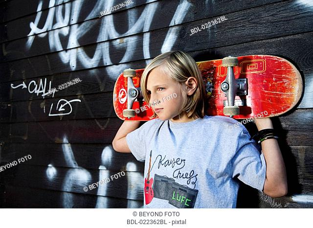 portrait of young boy with skateboard