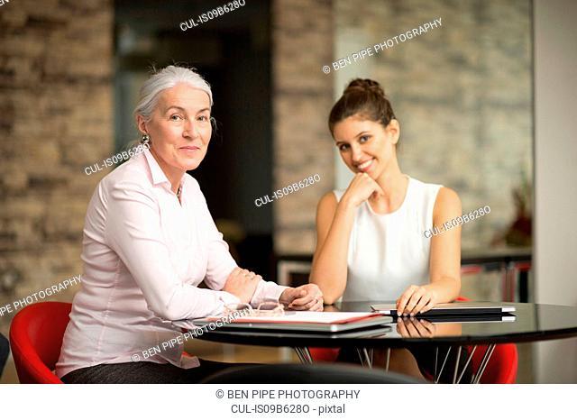 Portrait of two businesswomen at office desk