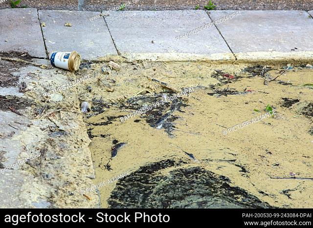 18 May 2020, Leipzig: A coffee mug is lying on the edge of a dirty pond. Photo: Gerald Matzka/dpa-Zentralbild/ZB. - Leipzig/Leipzig/Germany