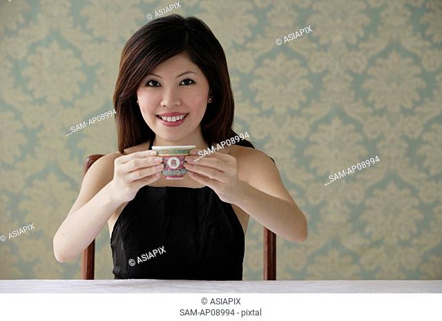 Young woman holding teacup with both hands