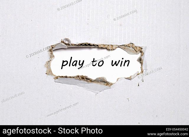 The word play to win appearing behind torn paper
