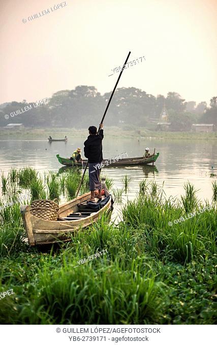 A fisherman in his boat at the Taungthaman Lake, Amarapura, Myanmar