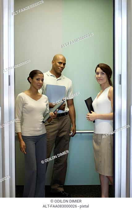 Young office workers standing in elevator