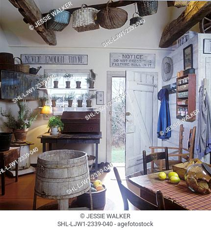 KITCHENS: Antique signs, baskets, furniture, washtub, terra cotta pots filled with herbs sit on shelves in front of window, distressed furniture, exposed beams