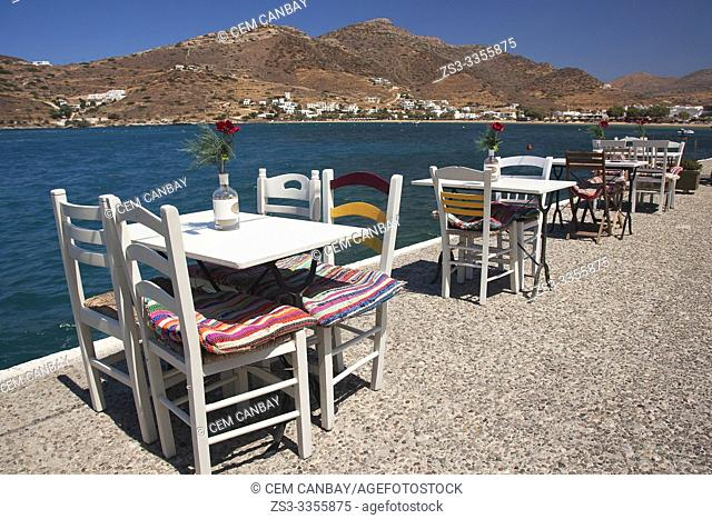 Tables and chairs of a traditional restaurant by the sea near the port, Ios Island, Cyclades Islands, Greek Islands, Greece, Europe