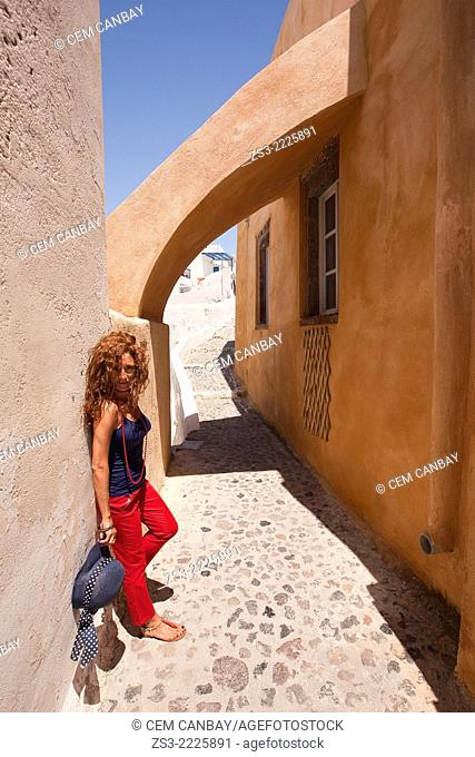 Woman posing in the alleys of Oia town, Santorini, Cyclades Islands, Greek Islands, Greece, Europe