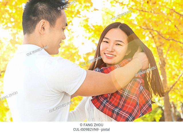 Young man wrapping tartan scarf around girlfriend in autumn park, Beijing, China