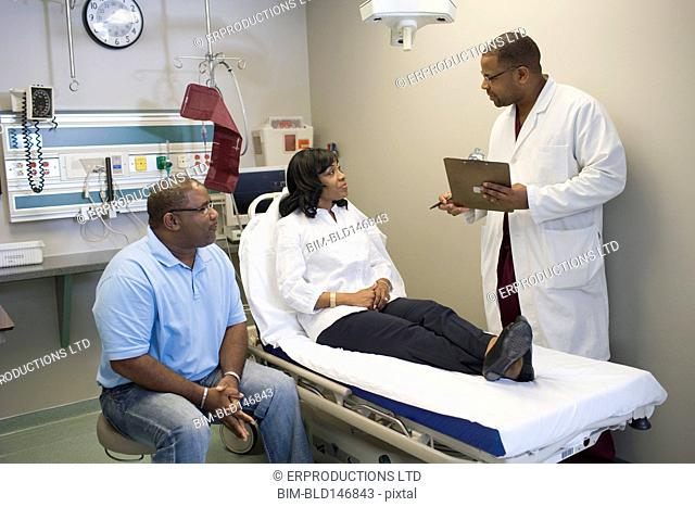 African American doctor talking to patient and her husband in hospital