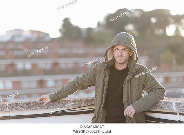 Man wearing hooded jacket standing on roof terrace
