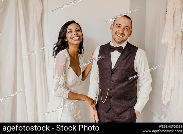 Bride and bridegroom smiling while standing at home