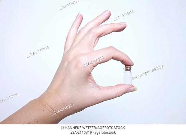 Hand Holding Little Glass Bottle, Hand Gesture, Studio shot