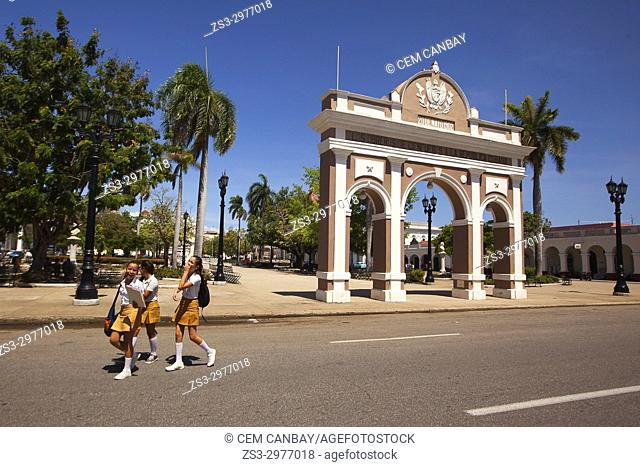Schoolgirls wearing uniforms in front of the Arch Of Triumph-Arco Del Triunfo at Parque Jose Marti in Plaza de Armas Square, Cienfuegos, Cuba, West Indies