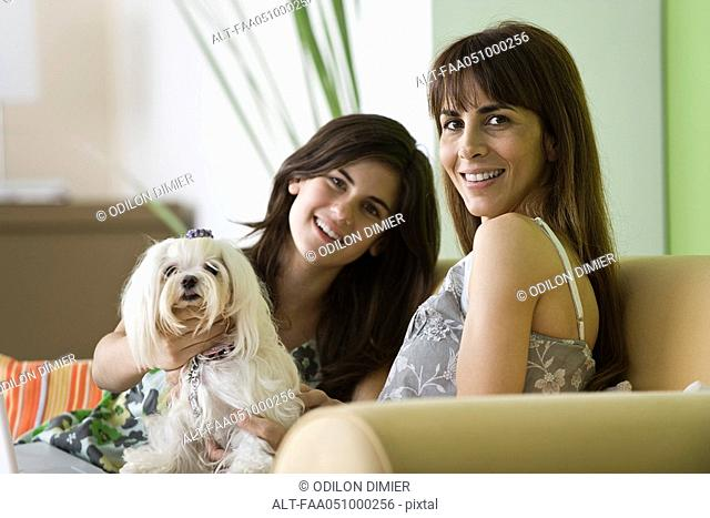 Mother and teenage daughter with pet dog, portrait