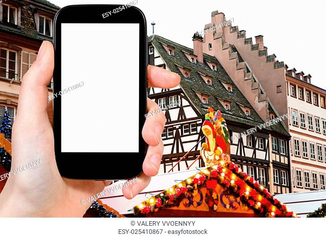 travel concept - tourist photograph Christmas market in medieval european town Strasbourg on smartphone with cut out screen with blank place for advertising...