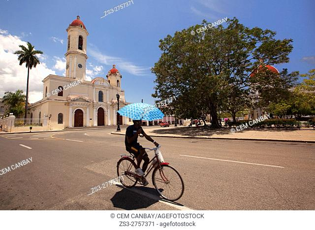 Cyclist carrying an umbrella in front of the Purisima Concepcion Cathedral in Jose Marti Park, Cienfuegos, Cuba, West Indies, Central America