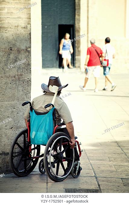 Man in wheelchair at the Cathedral of Valencia with cowboy hat, Spain