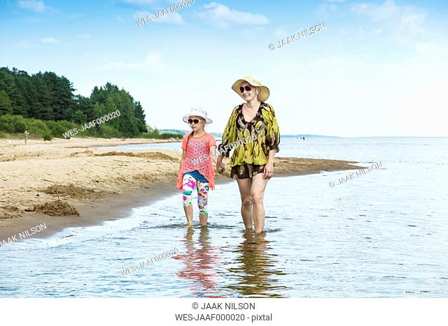 Estonia, Lake Peipus, Kauksi beach, mother and daughter walking in shallow water