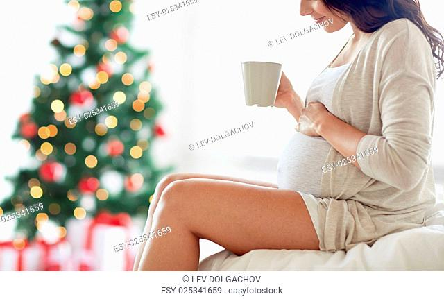 pregnancy, holidays, drinks, people and expectation concept - close up of happy pregnant woman with cup drinking tea sitting on bed at home bedroom over...